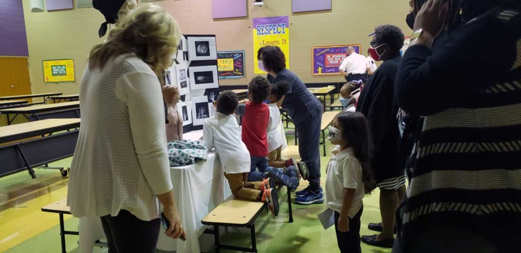 group of people including children looking at a display