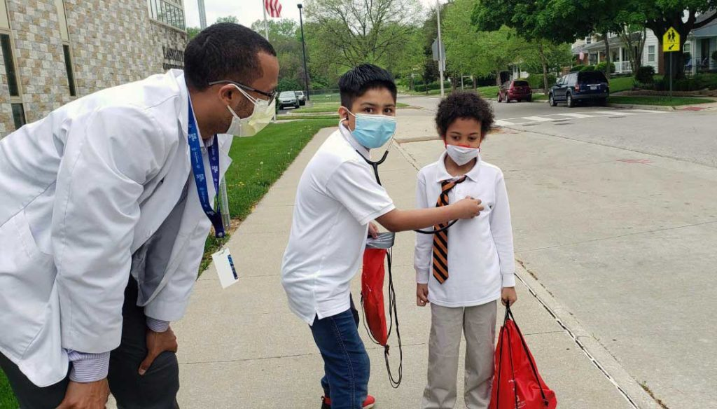 child listening to another child's pulse with a stethoscope while an adult watches
