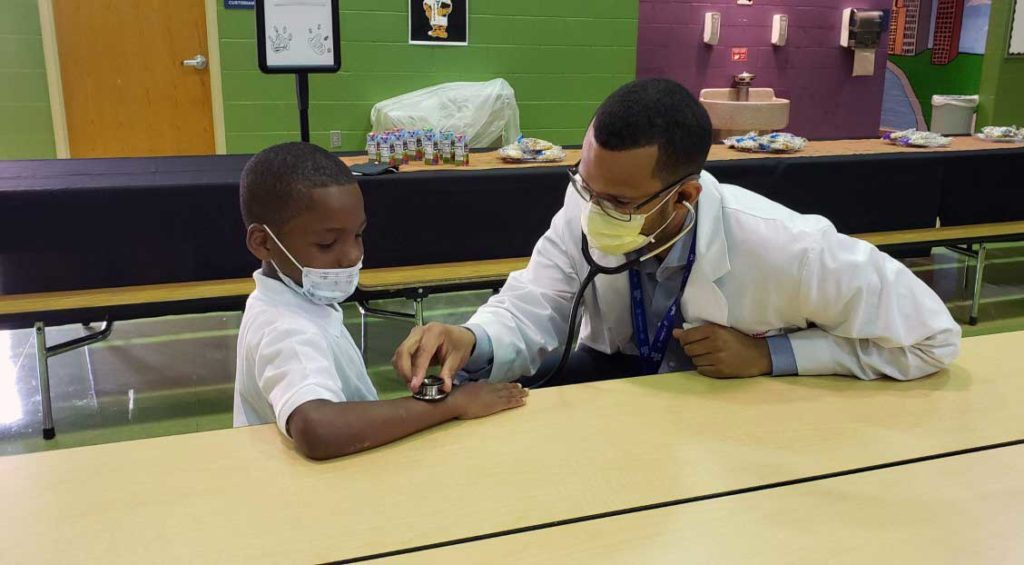 adult checking child's pulse with a stethoscope
