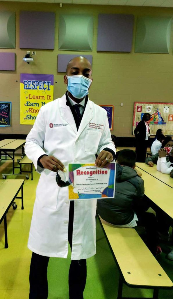 adult in labcoat holding a recognition certificate